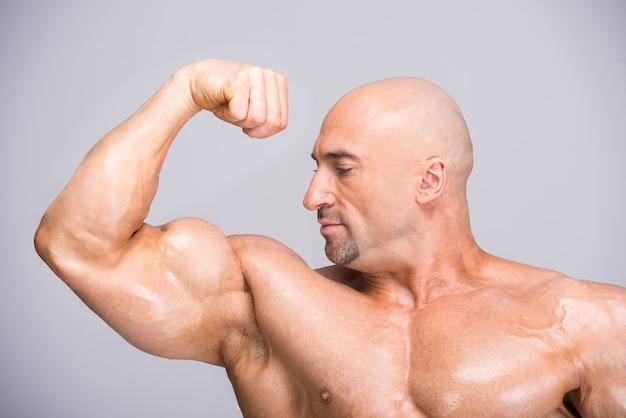 L'homme contracte son biceps et la regarde.