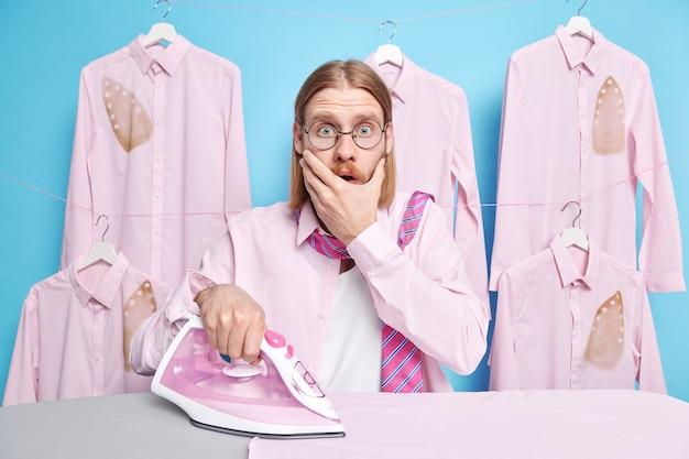 L'homme contre la bouche regarde effrayé a oublié une tâche de plus de la femme à propos des poses de la maison près de la planche à repasser caresse les vêtements bleus