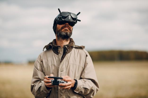 Homme contrôlant un drone quadricoptère fpv pour la photographie aérienne et la vidéographie avec télécommande d'antenne casque.
