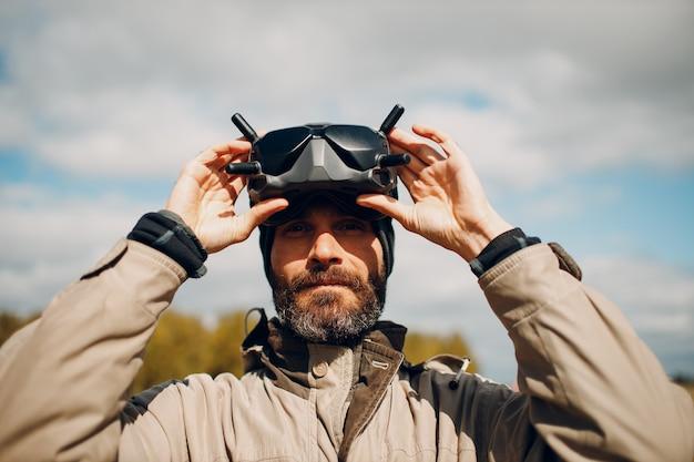 Homme contrôlant un drone quadricoptère fpv pour la photographie aérienne et la vidéographie avec télécommande d'antenne de lunettes.