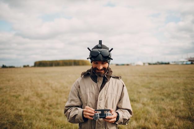 Homme contrôlant un drone quadricoptère fpv avec une télécommande d'antenne de lunettes