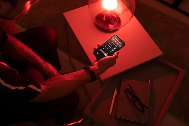 Homme contrôlant une lampe intelligente avec son téléphone