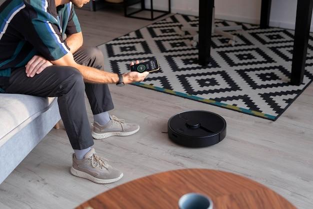 Homme contrôlant un robot aspirateur avec son téléphone