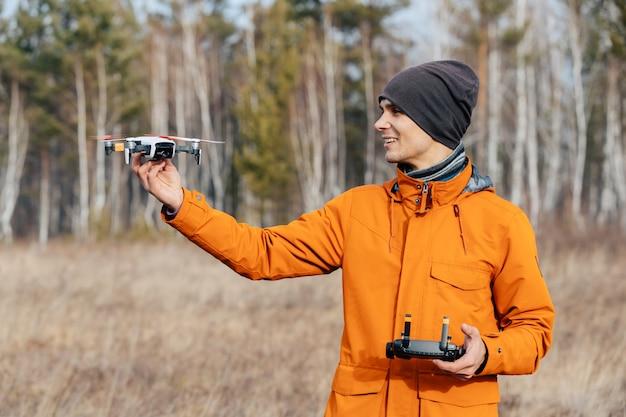 Un homme contrôle un drone quadcopter à l'extérieur en automne. le gars tend la main au drone.