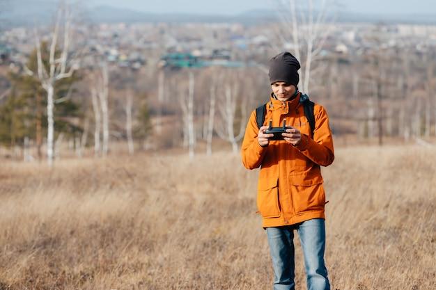 Un homme contrôle un drone quadcopter à l'extérieur en automne.