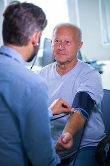 Homme contrôle de la pression artérielle du patient, le médecin