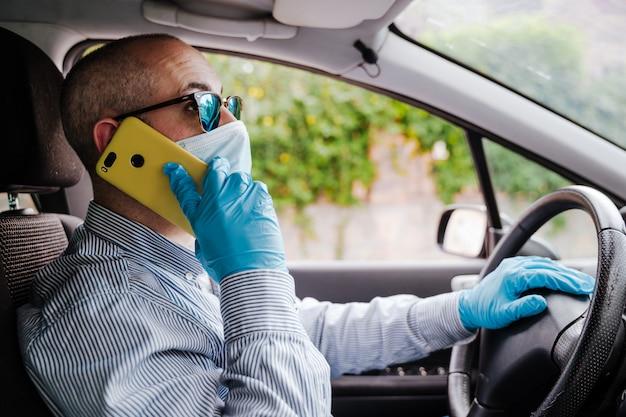 Homme, conversation téléphone mobile, dans voiture, porter, masque protecteur, et, gants
