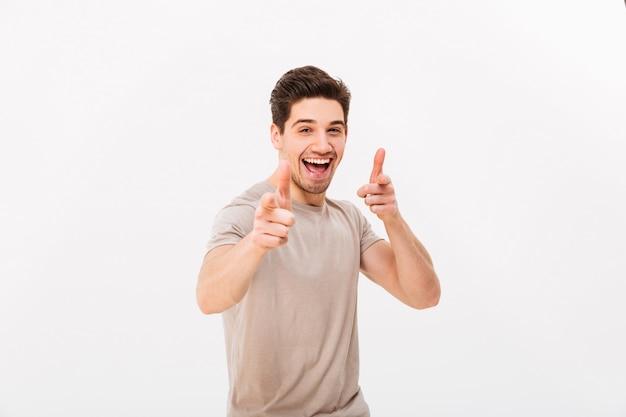 Homme cool caucasien en t-shirt beige, gesticulant des index sur l'appareil photo, ce qui signifie hey you ou bonne chance, isolé sur mur blanc