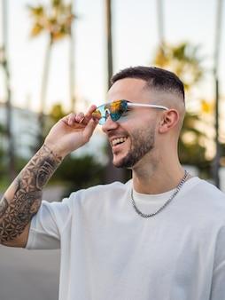 Homme cool espagnol avec des tatouages et des lunettes de soleil