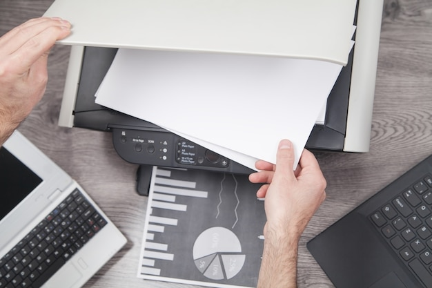 Homme copiant et numérisant des documents au bureau.