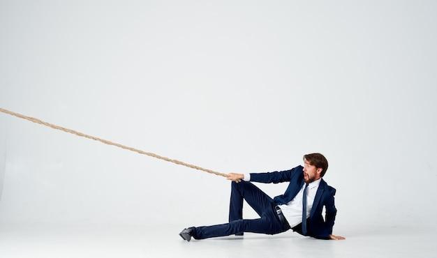 Homme avec une corde à la main sur la finance d'entreprise fond clair