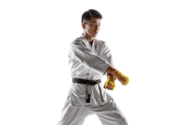 Homme coréen confiant en kimono pratiquant le combat au corps à corps, les arts martiaux. jeune combattant masculin avec une formation de ceinture noire isolée sur un mur blanc. concept de mode de vie sain, sport.