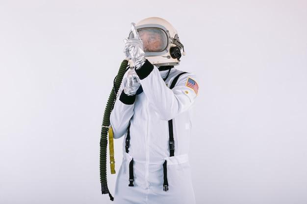 Homme cosmonaute en combinaison spatiale et casque, pointant le doigt vers le ciel, sur fond blanc.