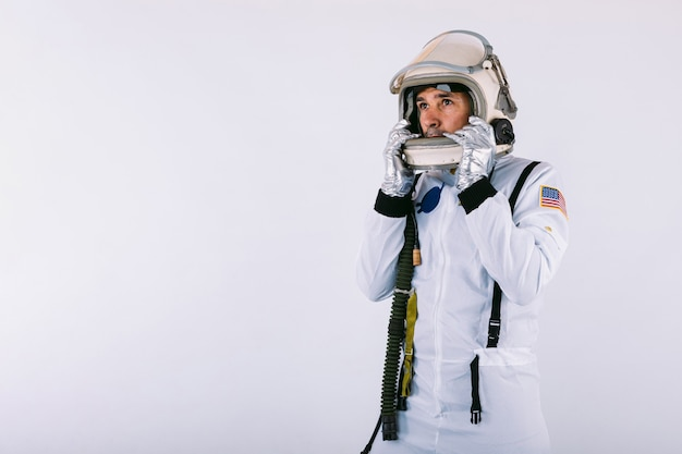 Homme cosmonaute en combinaison spatiale et casque tenant un casque avec les mains sur fond blanc