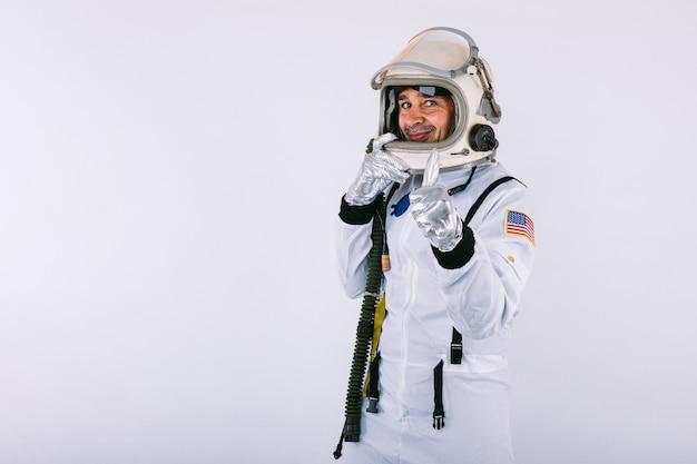 Homme cosmonaute en combinaison spatiale et casque, tenant le casque avec les mains et souriant, sur fond blanc.