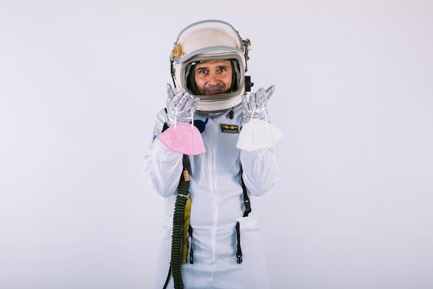 Homme cosmonaute en combinaison spatiale et casque, tenant deux masques fpp2, sur fond blanc. covid-19 et concept de virus