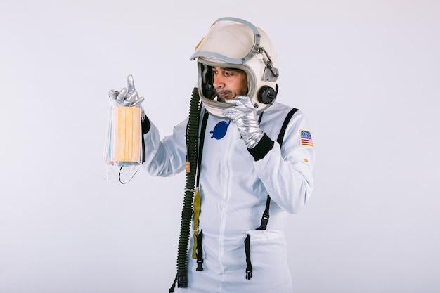 Homme cosmonaute en combinaison spatiale et casque, tenant de nombreux masques chirurgicaux colorés en forme d'éventail, sur fond blanc. covid-19 et concept de virus