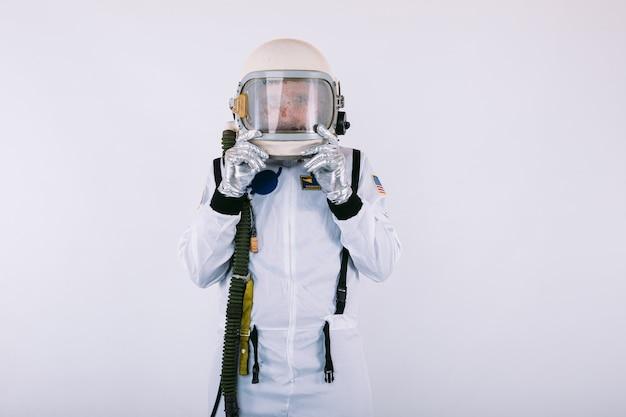 Homme cosmonaute en combinaison spatiale et casque, avec visage surpris tenant le casque avec ses mains, sur fond blanc.