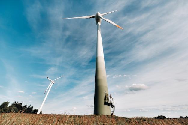 Un homme en costume d'affaires avec une chemise de golf verte se tient à côté d'un moulin à vent sur fond de champ et de ciel bleu. homme d'affaires près des moulins à vent. concept moderne du futur.