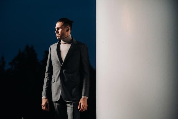 Un homme en costume d'affaires gris se tient à côté d'un moulin à vent après le coucher du soleil. homme d'affaires près des moulins à vent la nuit. concept moderne de l'avenir.