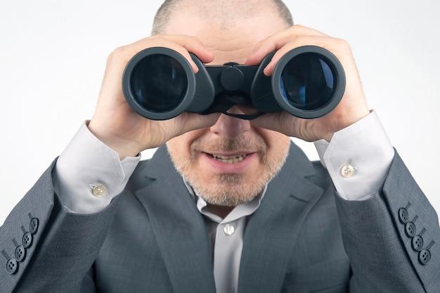 L'homme en costume d'affaires regarde à travers des jumelles. objectifs dans une entreprise prospère.