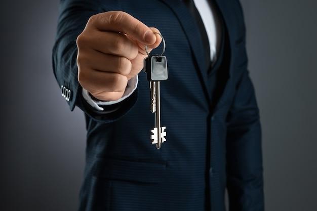 Un homme en costume d'affaires tient les clés dans sa main. le concept d'un agent immobilier, d'une hypothèque, de votre maison, d'un prêt immobilier. copiez l'espace.