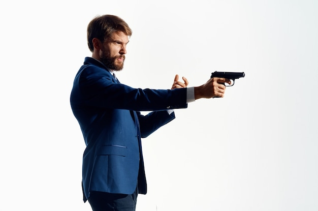 L'homme en costume agent secret avec une arme à feu dans les mains d'un fond clair de crime. photo de haute qualité