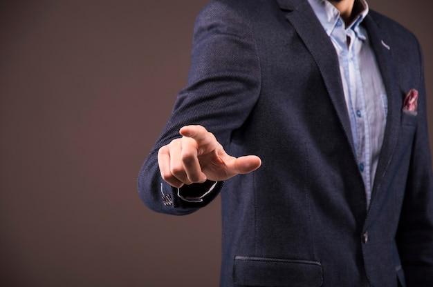 L'homme en costume appuie sur le doigt sur l'écran