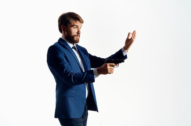 Homme en costume avec une arme à feu dans ses mains.