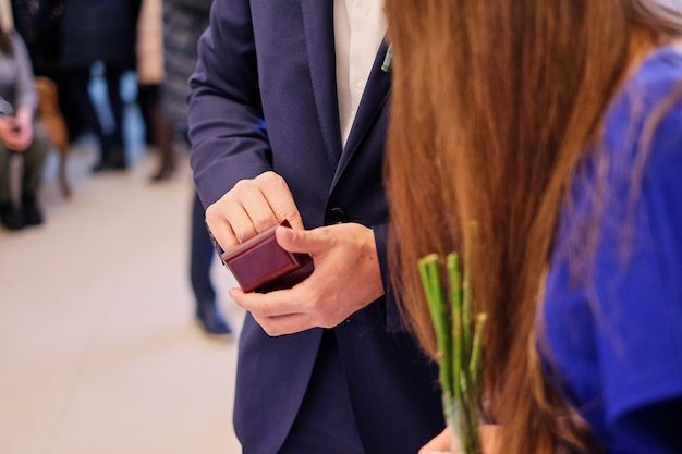 Un homme en costume bleu est titulaire d'une petite boîte cadeau d'alliances en bois. cadeau de mariage