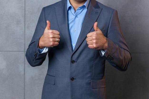 Un homme en costume bleu montre un geste avec ses mains