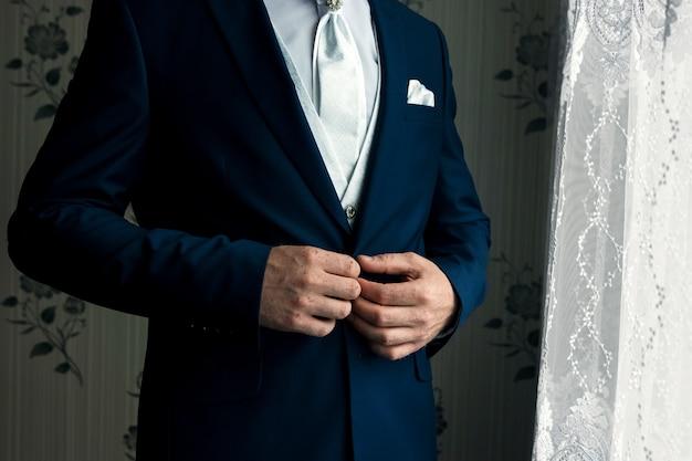 Un homme en costume bleu se redresse les manches
