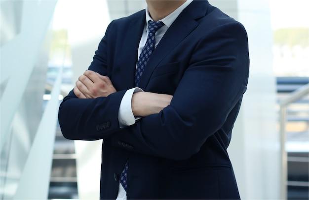 Homme en costume avec les bras croisés