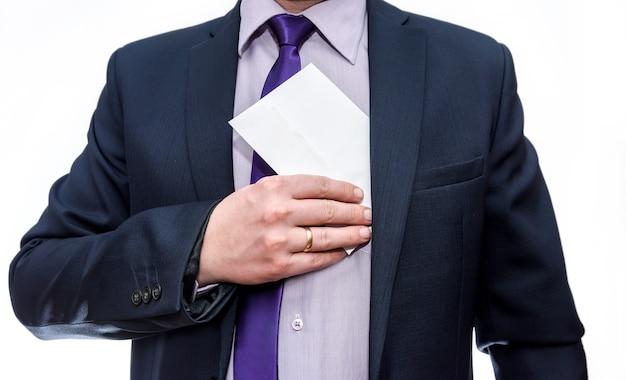 Homme en costume cachant une enveloppe dans la poche