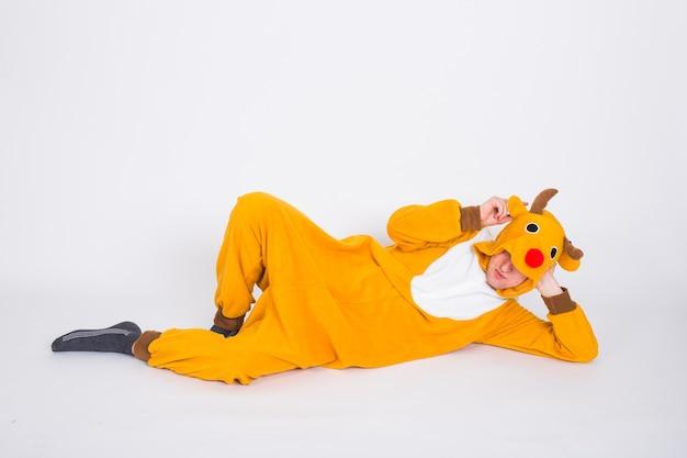 Homme en costume de cerf allongé sur le sol sur un mur blanc