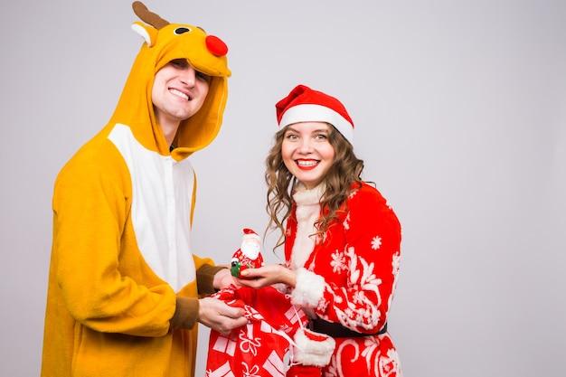 Homme en costume de cerf et femme en costume de père noël tenant une figurine de père noël dans les mains