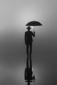 Homme en costume et chapeau avec un parapluie debout sur l'eau au lever du soleil