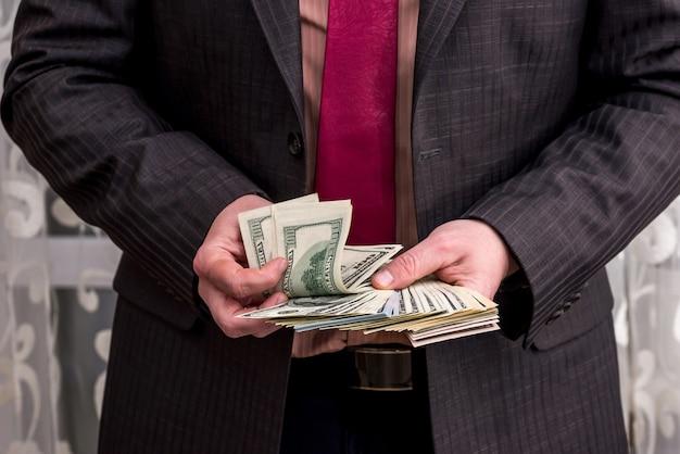 Homme en costume comptant les billets en dollars dans ses mains