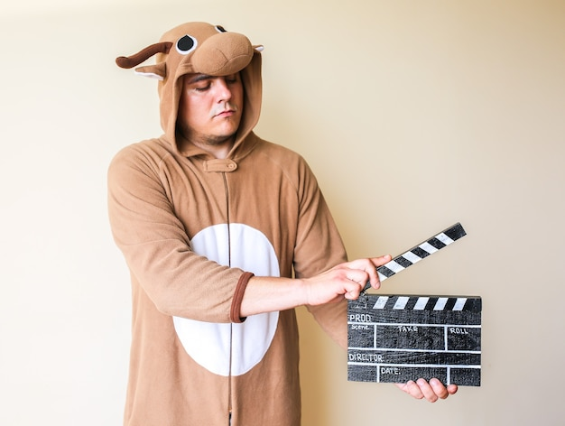 Homme en costume de cosplay tenant un clap noir. guy dans les vêtements de nuit drôles de pyjamas d'animaux faisant un film. réalisation et de film de cinéma amateur. concept créatif. anime japonais.