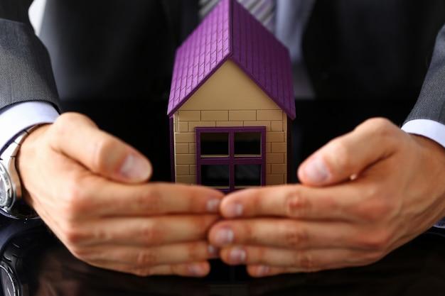 Homme en costume et cravate avec bras petite maison de jouet