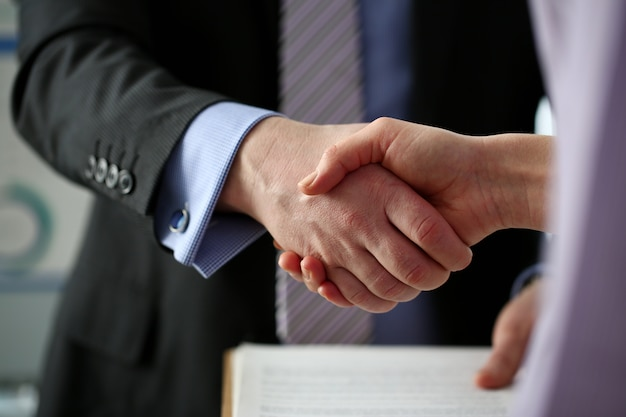 Homme en costume-cravate donne la main comme bonjour au bureau