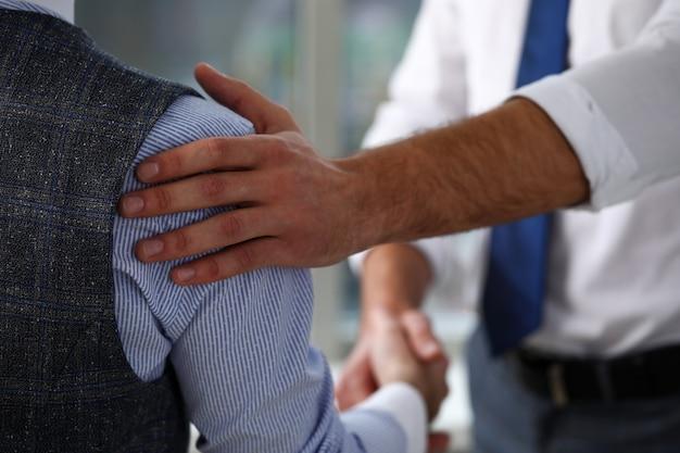 L'homme en costume et cravate donne la main comme bonjour en gros plan de bureau