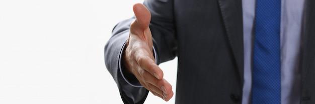 L'homme en costume et cravate donne la main comme bonjour