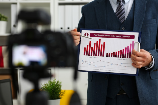 Homme en costume et cravate montrant le pavé graphique des statistiques