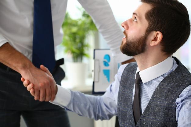 Homme en costume et cravate serrant la main avec un collègue