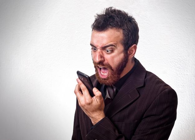 Homme en costume crier dans son téléphone portable