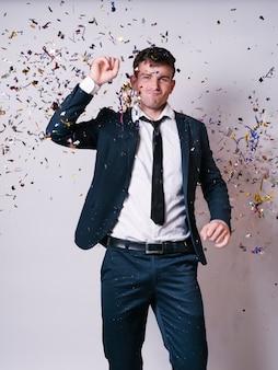 Homme en costume dansant sous les paillettes brillantes