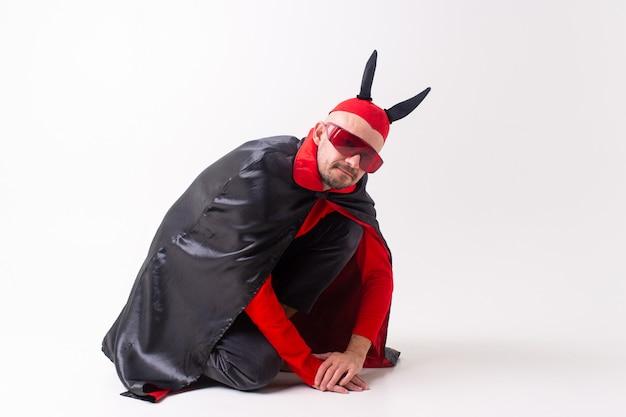 Homme en costume de diable posant.