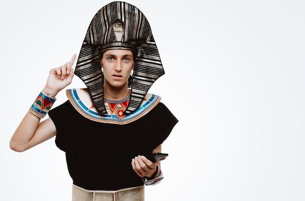 L'homme en costume égyptien antique holding smartphone pointant avec l'index vers le haut sur blanc