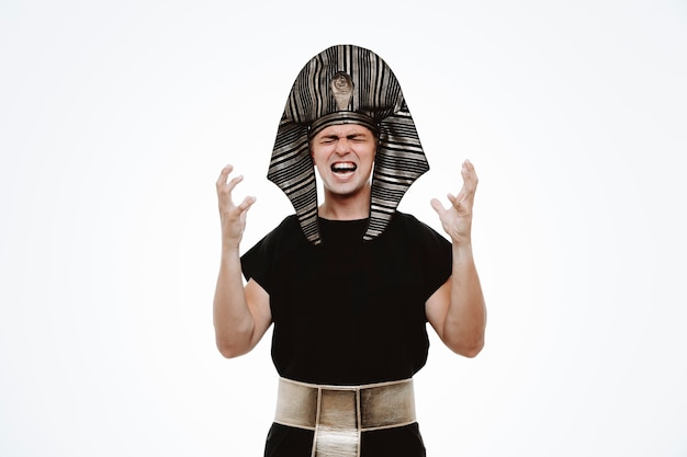 Homme en costume égyptien antique levant les bras en colère et frustré en criant sur blanc